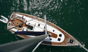 Barca's sailing wooden floor boat floating at the sea in Santorini top view