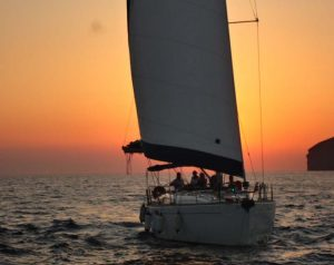 Barca sailing and some tourists enjoying the sunset in Santorini