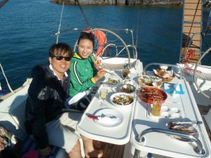A couple having a nice meal of traditional greek dishes inside barca's boat at Santorini