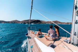 Three people enjoying the sea and the cruise relaxig on the deck of Barca's sailing boat in Santorini
